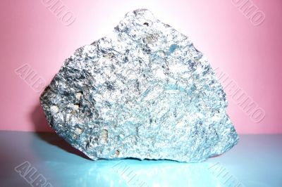 Gray shiny stone on a pink-blue background.