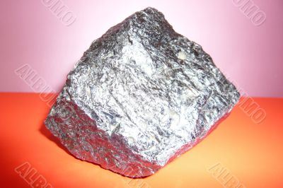 Gray shiny stone on a pink-red background.