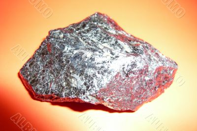 Gray shiny stone on a red background.