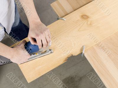 overhead image of a man cutting sheet of a wooden plank