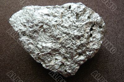 Silvery shiny stone on a dark brown background.
