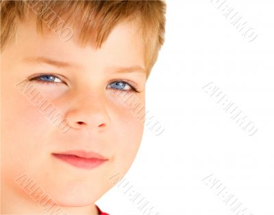 Blond boy with blue eyes looking at camera.