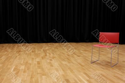 A directors chair on a stage with a blackcurtain in background