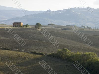 barn in a field with mountain range