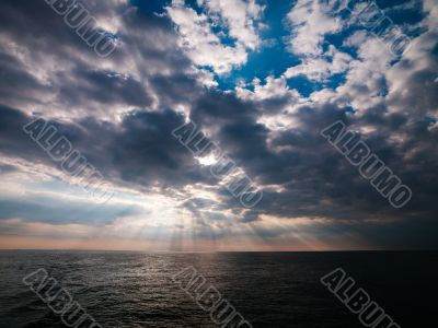 image of ocean and sun beams through clouds