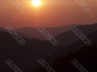 silhouette of mountains and sun