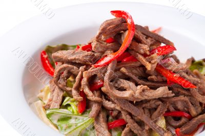 Salad of meat with red pepper on white plate