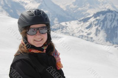 Young woman in ski clothes - mountains in the background
