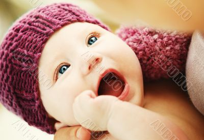 Beautiful newborn baby in a knit hat with beautiful blue eyes
