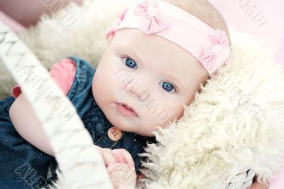 cute newborn baby girl in a basket on white fur