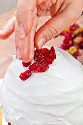 Hands decorating christmas cake