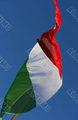 A large Italian flag in the blue sky free