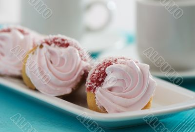 Three cakes with pink cream on a blue background
