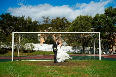 Bride and groom on the football field
