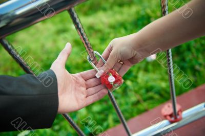 The bride and groom hold together their alliance lock