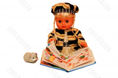 The doll is holding an open book.