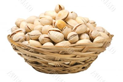 Pistachio nuts in a wicker plate, isolated