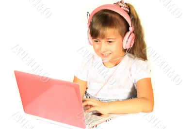 Beautiful little girl with headphones and a computer.