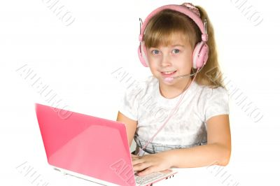Beautiful little girl with headphones and a computer
