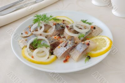 Slices of salted herring with onion, lemon and spices