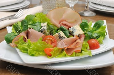 Appetizer with slices of jamon and blue cheese with cherry