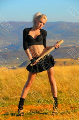 Sexy blonde girl with the bat against the sky