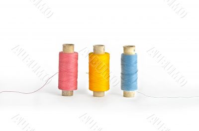Three colorful spools of thread