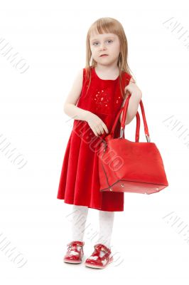 Fashion little girl with a red handbag, in catwalk model pose