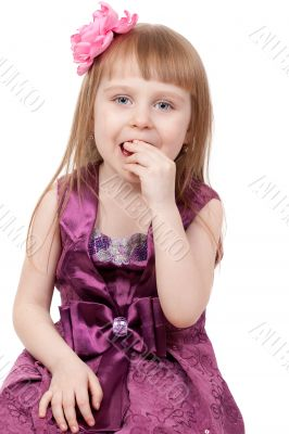 The little girl eats a candy. Isolated on a white background