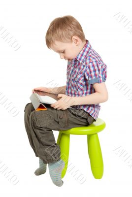 boy with a Tablet PC sitting on a green children`s chair