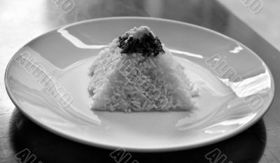 pyramid of rice on a plate in a restaurant with a worn table