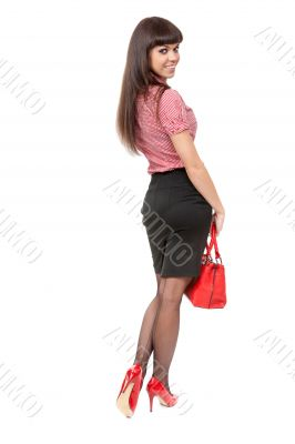 Beautiful slim girl in high heel shoes with a stylish red bag in
