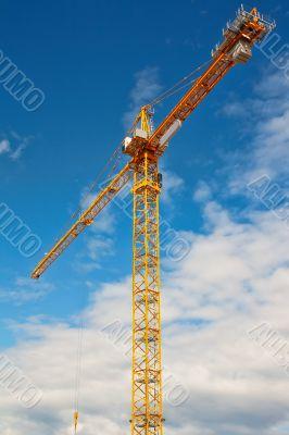 Tall white tower crane against bright blue sky.