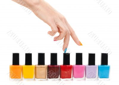 Female hand fingers are the colored paints polish on a white bac