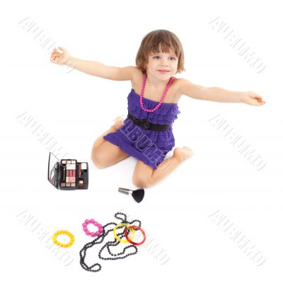 Cute little girl with makeup, necklaces and bracelets is in adul