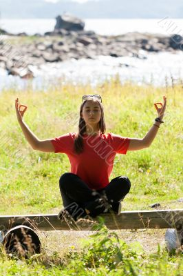 girl in a red dress sitting on a bench in the lotus position