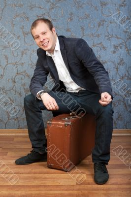A young man sits on an old brown suitcase in the interior