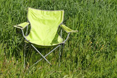 Green folding chair on the grass
