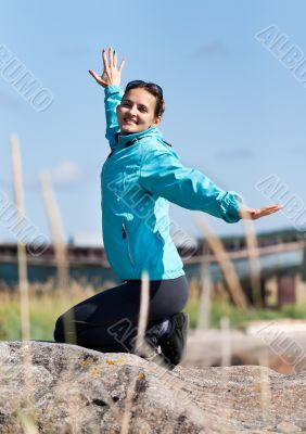 Beautiful girl in a jacket kneeling on a rock