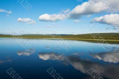 Calm beautiful rural landscape with a lake and sky reflected