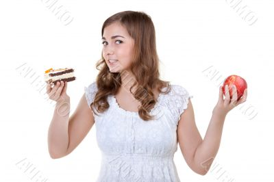 Young beautiful female choose from sweet cake and red apple