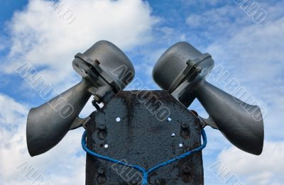 Outdoor public address loudspeakers against a blue sky