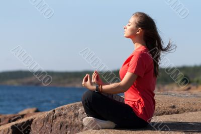 Young girl in lotus pose on the rocks