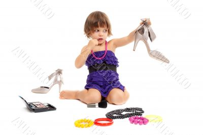 Cute little girl with cosmetics and women`s shoes in the studio