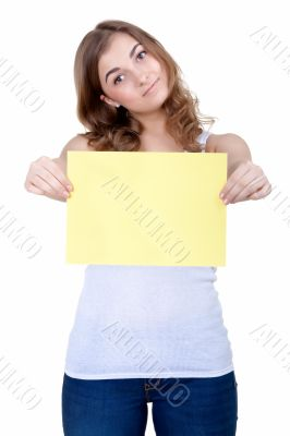 Beautiful young girl shows a blank sheet of yellow