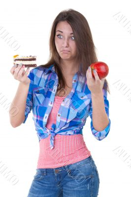 Girl in doubt with an apple and a cake