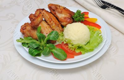 Baked chicken wings with garlic and potatoes and vegetables