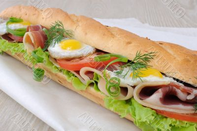 Big sandwich with ham, tomato and quail egg