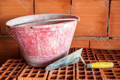 Trowel, bucket and bricks