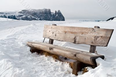 isolated bench in snow scape